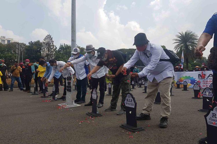 Aksi 'Kubur Omnibus Law' oleh buruh di sekitar kawasan Patung Kuda, Jakarta, pada aksi Hari Buruh (1/5/2021).