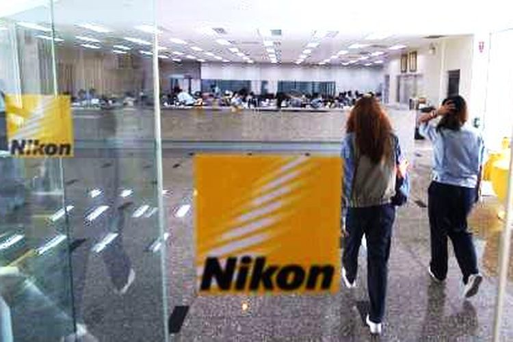 Karyawan berjalan di lobi pabrik Nikon Thailand Co.Ltd yang berada di kawasan industri Rojana, Ayutthaya, Thailand, Jumat (10/10/2014). Nikon Thailand mulai beroperasi pada 1990, dan saat ini mempekerjakan 7.404 karyawan.