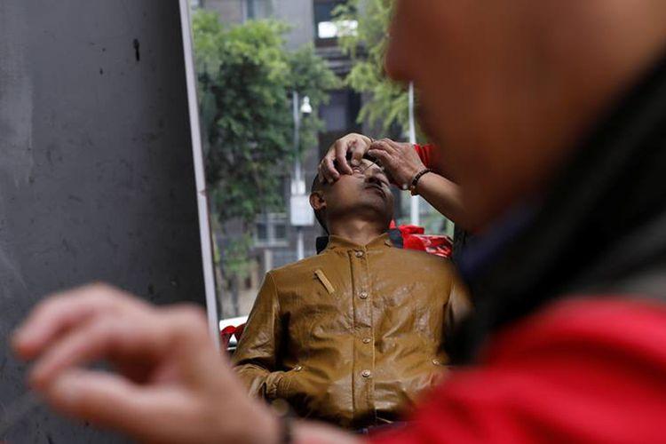 Seorang pelanggan dari Xiong Gaowu, pria 62 tahun yang menjalankan praktik pangkas kelopak mata di pinggir jalan Kota Chengdu, Provinsi Sichuan, China. Foto ini diambil pada 18 November 2017.