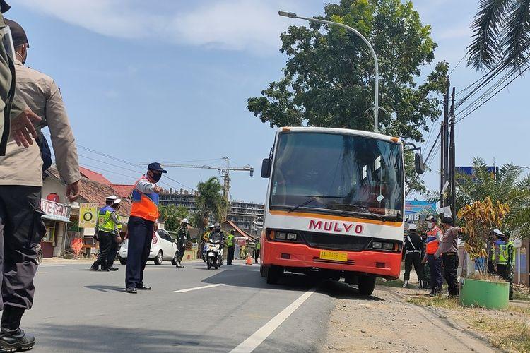 Aparat memeriksa kendaraan berpenumpang di jalur provinsi di wilayah Kapanewon Temon, Kabupaten Kulon Progo, Daerah Istimewa Yogyakarta. Kebijakan peniadaan mudik membuat banyak kendaraan mengangkut pemudik terpaksa harus putar balik.