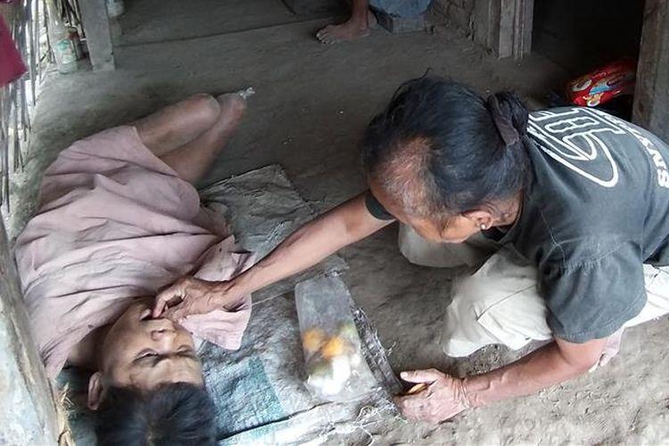 Mbah Miratun menyuapi roti pemberian warga kepada adiknya Mesinem yang lumpuh total dan mengalami keterbelakangan mental.