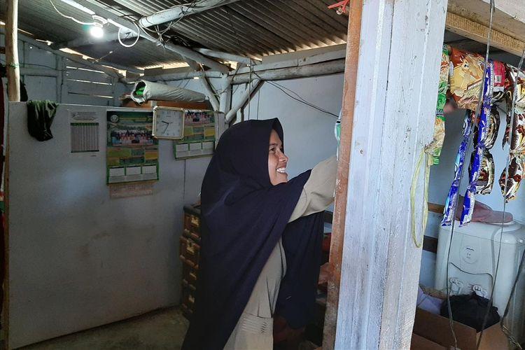 Nining Suryani (44) menunjukkan isi rumahnya yang menempati bagian toilet sekolah di SDN Karyabuana 3, Kecamatan Cigeulis, Kabupaten Pandeglang, Banten, Senin (15/7/2019)