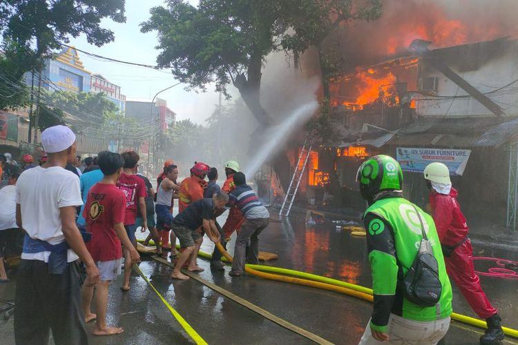 Petugas pemadam kebakaran bersama warga memadamkan api yang membakar 40 rumah di Jalan Payakumbuh RT. 07 RW. 09 Kelurahan Pasar Manggis, Setiabudi, Jakarta, Selasa (7/7/2020).