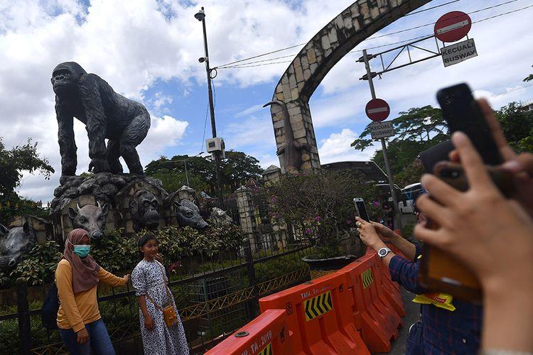 Warga berfoto di kawasan Taman Margasatwa Ragunan, Jakarta Selatan, Jumat (25/12/2020). Pemerintah Provinsi DKI Jakarta menutup area publik dan sejumlah tempat wisata termasuk Taman Margasatwa Ragunan selama masa libur perayaan Hari Natal dan Tahun Baru pada 25 dan 31 Desember 2020, serta 1 Januari 2021.