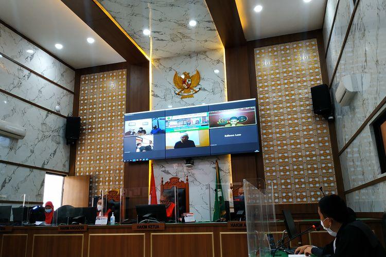 Terdakwa kasus rekayasa isu babi ngepet di Depok, AI (tengah bawah layar), diminta hadir langsung ke Pengadilan Negeri Depok untuk mengikuti sidang perdana, Selasa (14/9/2021).