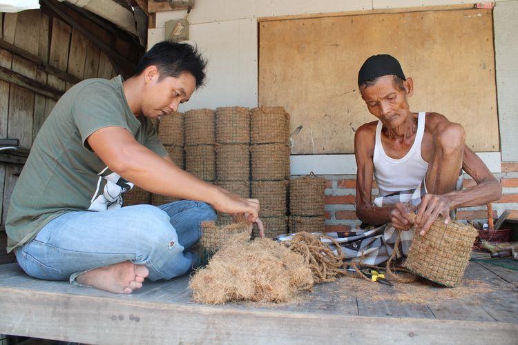 Muhammad David Mauli Niam (31), seorang guru honorer di MTs Negeri 4 Demak bersama Mbah Paidi (80) saat membuat pot sabut kelapa di rumahnya Desa Cangkring Kecamatan Karanganyar Kabupaten Demak Jawa Tengah,. Jumat (11/9/2020)