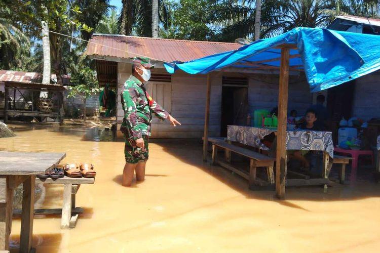 Babinsa Koramil 16/Tapung, Serda Rotoa Simarmata saat meninjau lokasi banjir dan mengimbau warga agar waspada apa bila air sungai kembali naik di Desa Sukaramai, Kecamatan Tapung Hulu, Kabupaten Kampar, Riau, Senin (27/9/2021).