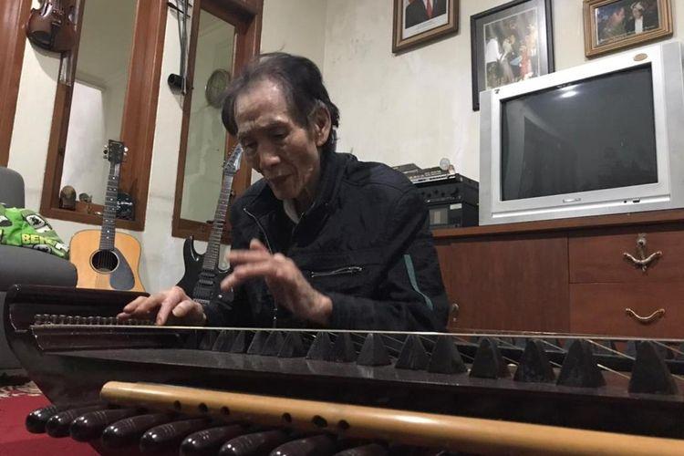 Budayawan sekaligus maestro musik sunda, Tan Deseng, tengah memainkan kecapi.