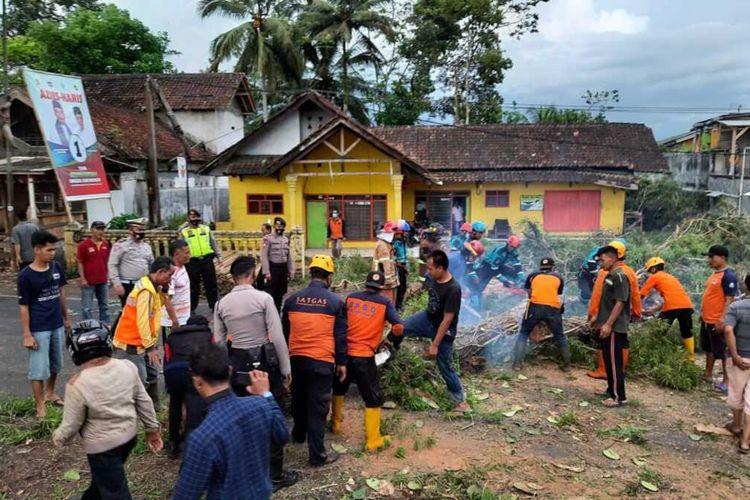 Petugas BPBD, Polri dan TNI Kabupaten Tasikmalaya sedang menyingkirkan pohon tumbang yang menghalangi akses jalan Tasikmalaya-Garut via Singaparna pada Minggu (1/11/2020) sore.