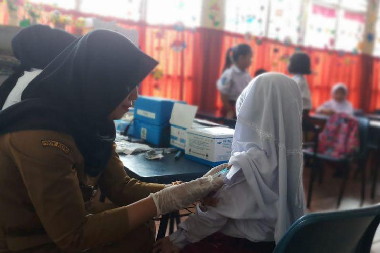 Salah seorang Dokter melakukan imunisasi Campak MR kepada salah seorang siswa SDN 02 Sekupang, Batam