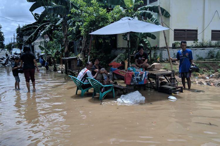Warga Kelurahan Gebang Raya Kecamatan Periuk Tangerang bersantai di tengah banjir, Rabu (26/2/2020)