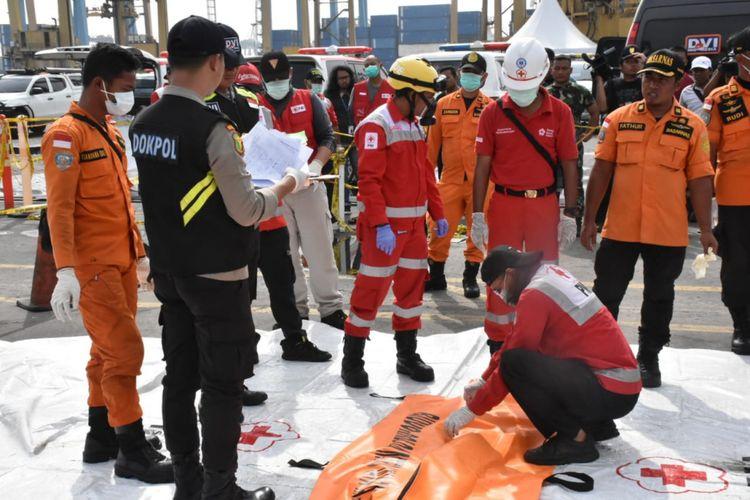Petugas memeriksa satu kantong jenazah yang tiba di Dermaga JICT 2 Pelabuhan Tanjung Priok, Jumat (9/11/2018).