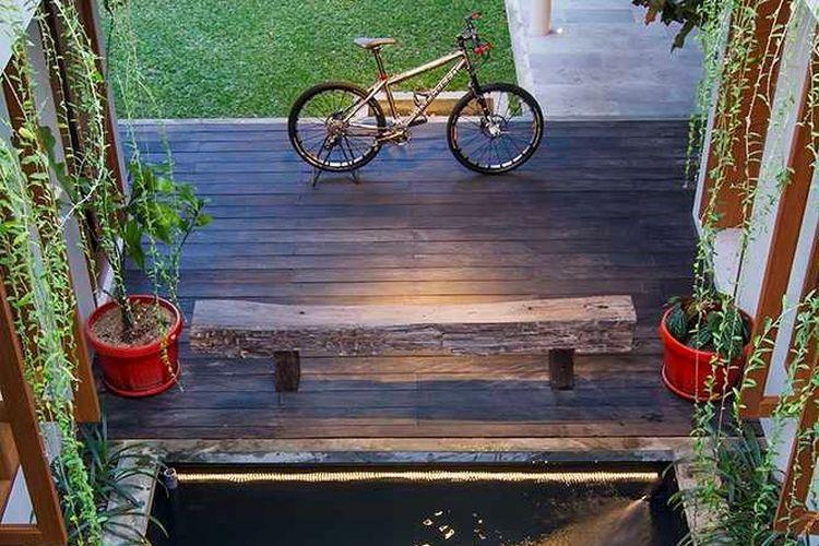 Lantai dan bangku kayu di dekat kolam ikan taman karya Erwin Kusuma