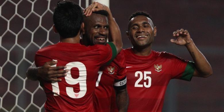 Pemain Indonesia Boaz Solossa (tengah) mendapat ucapan selamat dari rekannya, Titus Bonai (kanan), setelah berhasil mencetak gol ke gawang China pada babak kualifikasi Piala Asia 2015 di Stadion Utama Gelora Bung Karno, Jakarta, Selasa (15/10). Pertandingan berakhir imbang dengan skor 1-1.
