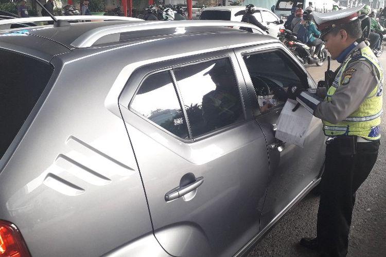 Seorang pengendara terjaring operasi ganjil genap di Jalan S Parman, Slipi Petamburan, Jakarta Barat, Rabu (1/8/2018).