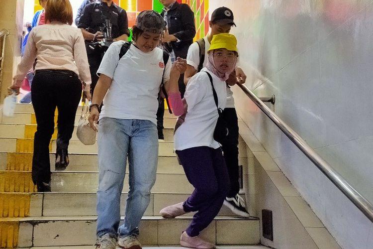 Icha (21), penyandang disabilitas harus turun dengan dituntun relawan di Terowongan Penyeberangan Orang, Kota Tua, Jakarta, Selasa (3/12/2019). Hal ini dikarenakan lift prioritas yang tak kunjung difungsikan.
