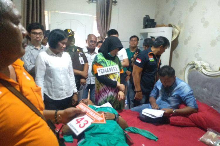 Zuraida Hanum, istri sekaligus otak pembunuhan hakim PN Medan Jamaluddin, mendengarkan polisi saat membacakan berita acara rekonstruksi pembunuhan hakim PN Medan, Jamaludin di dalam kamar.