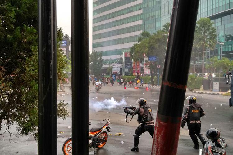 Seorang polisi menembakkan gas air mata ke arah massa aksi yang berhamburan setelah rusuh di depan gedung DPRD Sumut, Selasa sore tadi (24/9/2019).