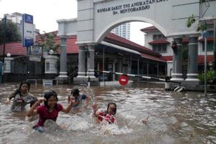 Anak-anak bermain di tengah banjir yang merendam kawasan Bendungan Hilir, Jakarta Pusat, Senin (13/1/2014).