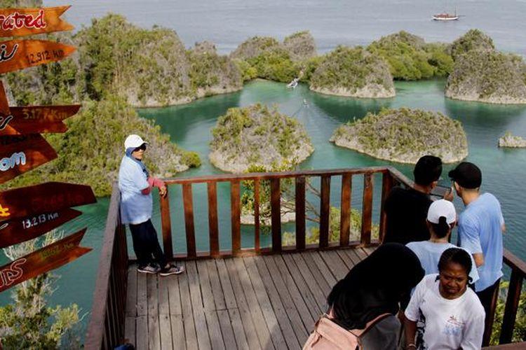 Wisatawan menikmati pemandangan gugusan pulau karst dari Bukit Piaynemo, Desa Pam, Kecamatan Waigeo Barat Kepulauan, Kabupaten Raja Ampat, Papua Barat, Senin (31/11/2016).