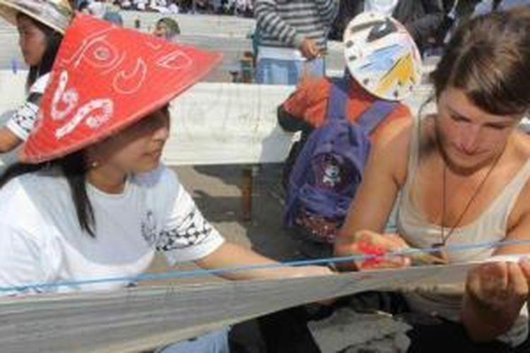 Sarah, pelancong asal Jerman, mengikuti acara membatik massal demi memecahkan rekor Muri, untuk memperingati Hari Batik Nasional, di Alun-Alun Utara Kota Yogyakarta, Kamis (2/10/2014).
