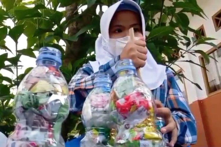Siswi SDN Sukatani Mayak Cianjur sedang mengerjakan daur ulang sampah model ecobrick dengan memanfaatkan limbah plastik.