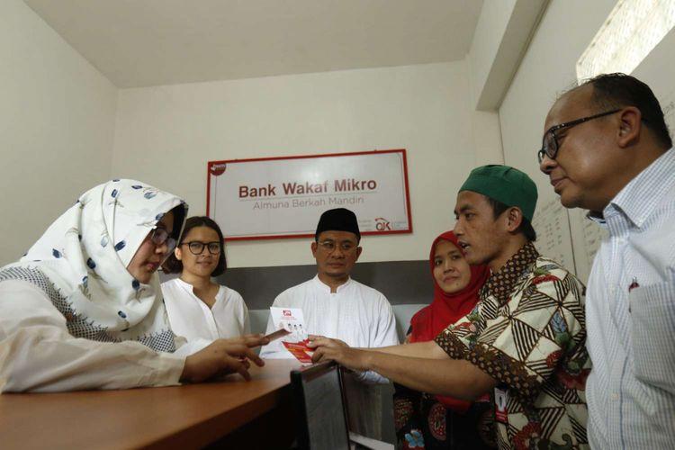 Deputi Komisioner Manajemen Strategis dan Logistik Otoritas Jasa Keuangan Anto Prabowo (kanan) dan Direktur Penelitian, Pengembangan, Pengaturan, dan Perizinan Perbankan Syariah Deden Firman Hendarsyah, mengamati kegiatan di Bank Wakaf Mikro, Pesantren Al-Munawwir, Krapyak, Bantul, DI Yogyakarta, Sabtu (5/5/2018). Bank Wakaf Mikro merupakan komitmen  OJK bersama pemerintah untuk terus memperluas penyediaan akses keuangan masyarakat, khususnya bagi masyarakat menengah dan kecil.