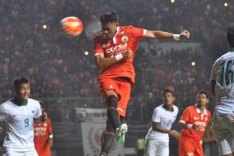 Bek Persija, Maman Abdurrahman melakukan lompatan sambil menyundul bola ke arah gawang timnas U-22 Indonesia pada uji coba di Stadion Patriot, Kota Bekasi, Rabu (5/4/2017) malam.
