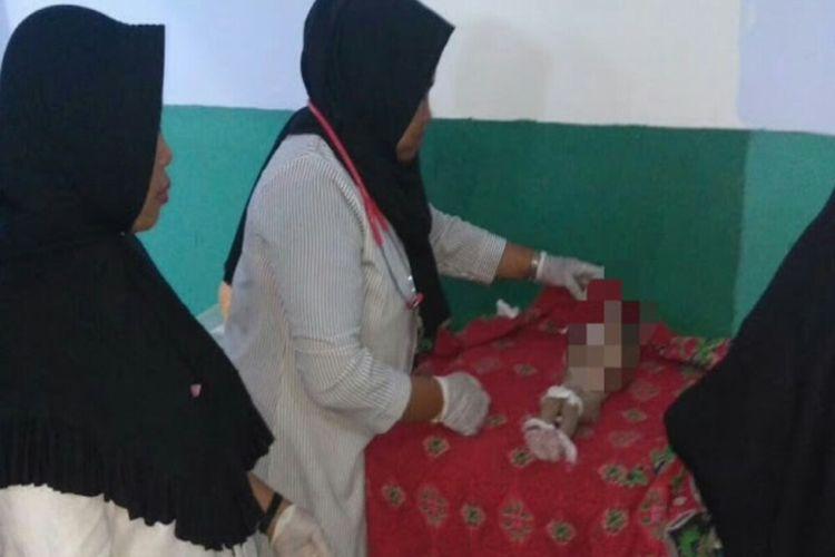 Jasad bayi malang yang ditemukan di selokan saat disemayamkan di Puskesmas Sape