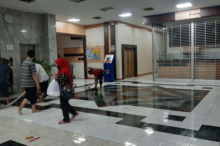 Petugas membersihkan lantai setelah genangan air memasuki Gedung B, Kantor Gubernuran Jateng, Selasa (23/2/2021).