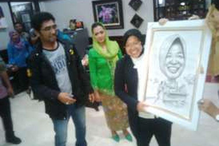 Risma diberi kado karikatur oleh wartawan, Rabu (23/11/2016).