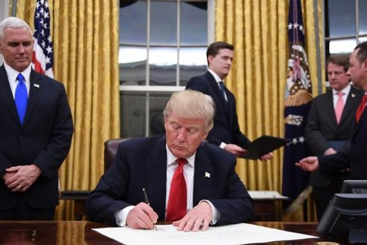 Presiden AS Donald Trump menandatangani sejumlah dokumen perintah eksekutifnya di Ruang Oval, Gedung Putih, disaksikan wakil presiden Mike Pence.
