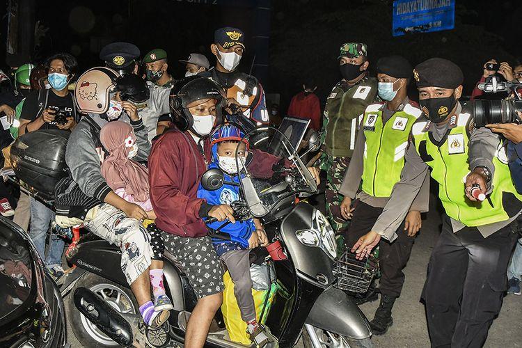Sejumlah petugas Kepolisian memutarbalikkan pemudik motor yang akan melintas di posko penyekatan mudik di Kedungwaringin, Kabupaten Bekasi, Jawa Barat, Minggu (9/5/2021). Pada H-3 jelang Hari Raya Idul Fitri 1422 H petugas gabungan dari TNI,Polri, Dishub dan Satpol PP memperketat penjagaan pemudik di perbatasan Kabupaten Bekasi dan Karawang.