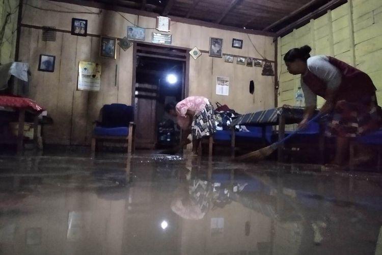 Partiwi (kiri) membersihkan lumpur akibat banjir yang menggenangi kediamannya, Kamis (18/3/2021) petang.
