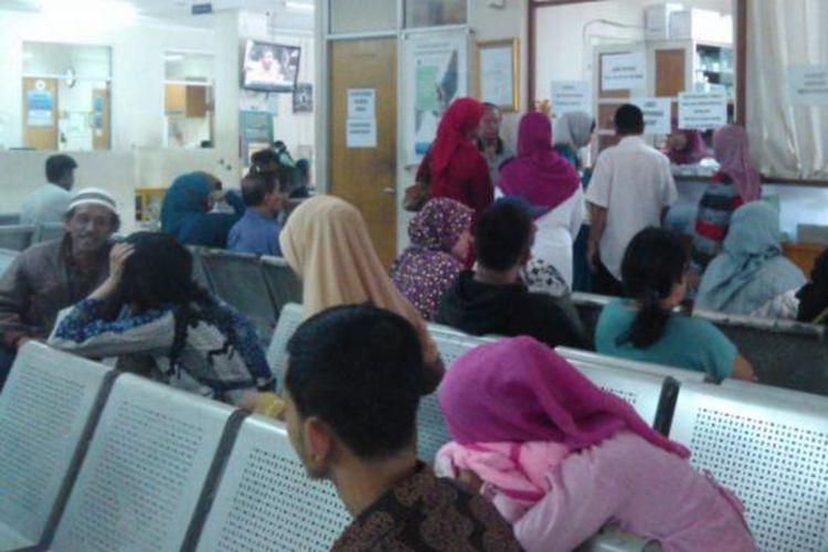 Para pasien yang mengantre sejak dini hari akhirnya bisa berobat dan terlihat tengah mengantre obat di loket RSUD Depok, Kamis (11/9/2014).