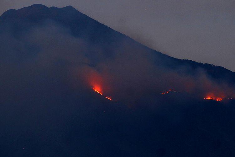Api membakar hutan di lereng Gunung Arjuno terlihat dari Desa Landungsari, Malang, Jawa Timur, Jumat (11/10/2019). Kawasan hutan yang terbakar berada di petak Curah Seriti di ketinggian 2.300 mdpl dengan kemiringan 70 derajat sehingga menjadi kendala bagi petugas untuk memadamkan api.