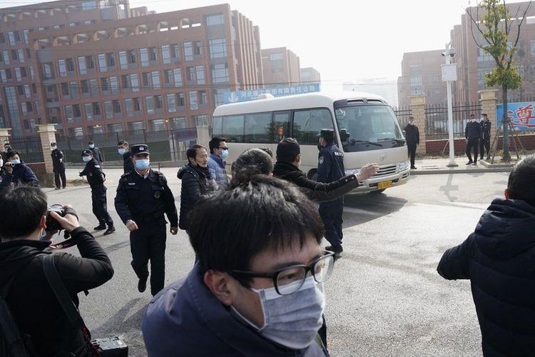 Jurnalis dan personel keamanan berkumpul di dekat pintu masuk Institut Virologi Wuhan setelah kunjungan tim Organisasi Kesehatan Dunia (WHO) di Wuhan di provinsi Hubei China pada Rabu, 3 Februari 2021.