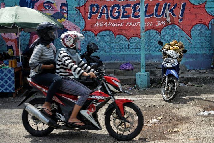 Warga melintasi mural bertema COVID-19 di kawasan Serangan, Yogyakarta, Selasa (1/12/2020). Gubernur DIY Sri Sultan HB X kembali memperpanjang status tanggap darurat bencana wabah COVID-19 hingga 31 Desember 2020 menyusul naiknya kasus penularan COVID-19 di DIY. ANTARA FOTO/Andreas Fitri Atmoko/rwa.