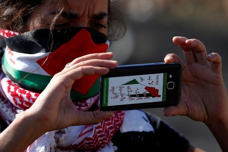 Seorang warga Palestina mengambil gambar menggunakan telepon genggamnya dalam salah satu unjuk rasa menentang pendudukan Israel.