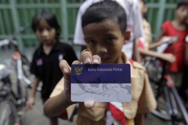 Warga menunjukkan Kartu Indonesia Sehat (KIS), Kartu Indonesia Pintar, dan Kartu Keluarga Sejahtera di Kantor Pos Kampung Melayu, Jalan Jatinegara Barat, Jakarta Timur, Rabu (13/5/2015).