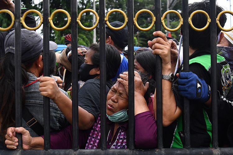 Warga antre berdesakan saat pembagian nasi kotak dan masker di Markas Komando Gabungan Wilayah Pertahanan (Kogabwilhan) I, Jakarta, Selasa (21/4/2020). Kegiatan tersebut merupakan kegiatan peduli dan berbagi dari Kogabwilhan-I kepada masyarakat sekitar di tengah berlangsungnya Pembatasan Sosial Berskala Besar.