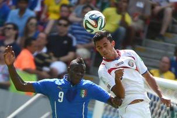 Penyerang tim nasional Italia, Mario Balotelli, berebut bola dengan bek Kosta Rika, Giancarlo González, pada pertandingan lanjutan penyisihan Grup D Piala Dunia di Itaipava Arena Pernambuco, Recife, Jumat (20/6/2014).