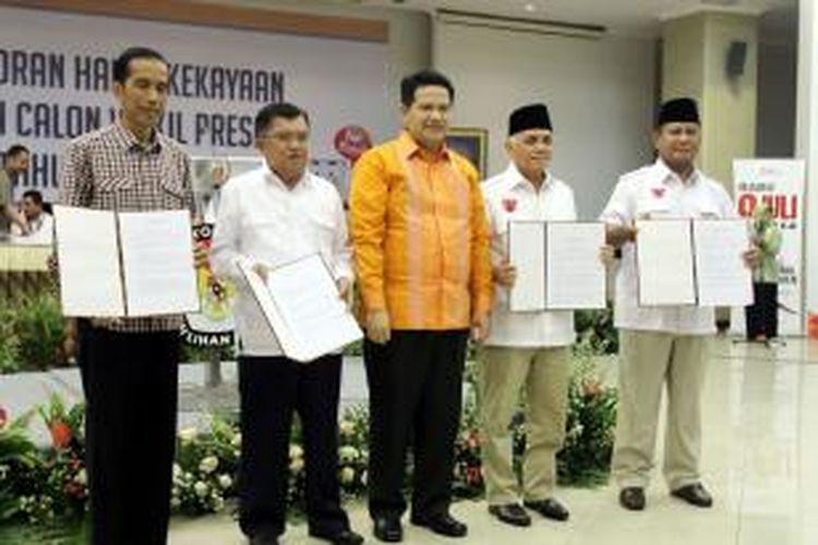 Ketua Komisi Pemilihan Umum Husni Kamil Manik (tengah) bersama dua pasang capres dan cawapres saat pengumuman harta kekayaan di kantor KPU, Jakarta Pusat, Selasa (1/7/2014). Capres nomor urut 1, Prabowo Subianto memiliki harta kekayaan terbanyak, yaitu sebesar Rp 1,6 triliun, cawapres nomor urut 2, Jusuf Kalla sebesar Rp 465 miliar, cawapres nomor urut 1, Hatta Rajasa sebesar Rp 30 miliar, dan capres nomor urut 2, Joko Widodo sebesar Rp 29 miliar.