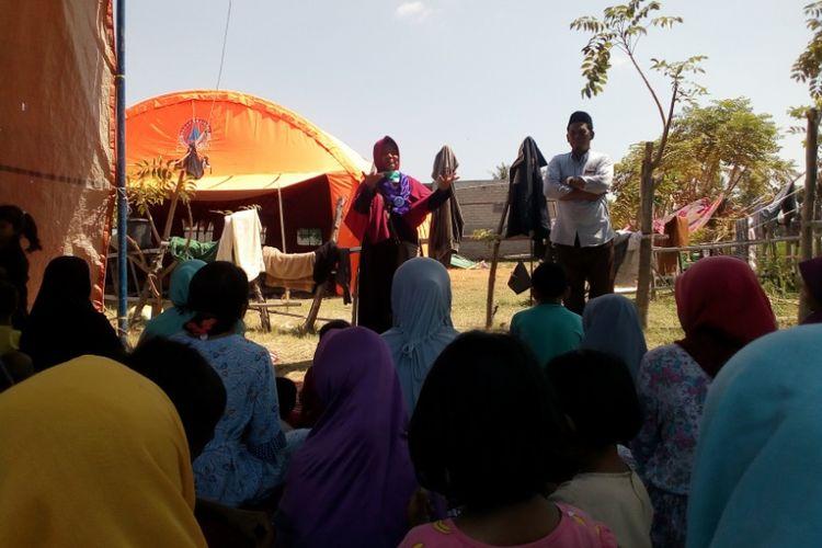 Yuli Suliswidiawati saat memandu sesi terapi di tenda pengungsian yang ada di kampung Gubug Baru, Desa Tanjung, Kecamatan Tanjung, Kabupaten Lombok Utara, Senin (20/8/2018).