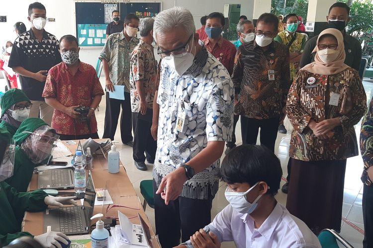 Gubernur Jateng Ganjar Pranowo berbincang dengan siswa saat meninjau pelaksanaan vaksinasi siswa usia 12-17 tahun di Solo, Jawa Tengah, Rabu (4/8/2021).