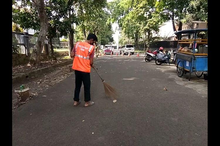 Warga dihukum menyapu oleh petugas karena tidak pakai masker saat beraktivitas di luar rumah, Jumat (15/5/2020)
