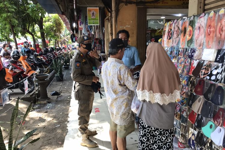 Pihak Satuan Polisi Pamong Praja (Satpol PP) bersama para Aparatur Sipil Negara (ASN) menegur pedagang-pedagang dan pengunjung di Pasar Kebayoran Lama yang tak menggunakan masker, Senin (6/7/2020).