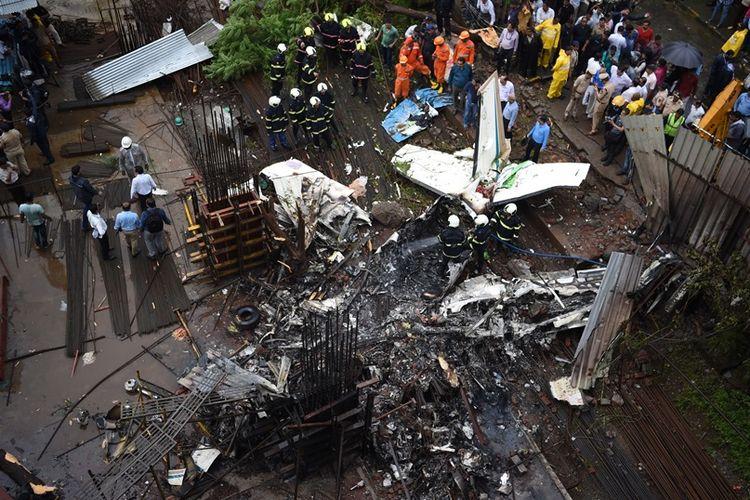 Petugas tim penyelamat memeriksa sisa-sisa badan pesawat yang jatuh dan terbakar setelah menabrak proyek konstruksi bangunan di Mumbai, India, Kamis (28/6/2018). Lima orang dilaporkan tewas akibat kecelakaan ini.