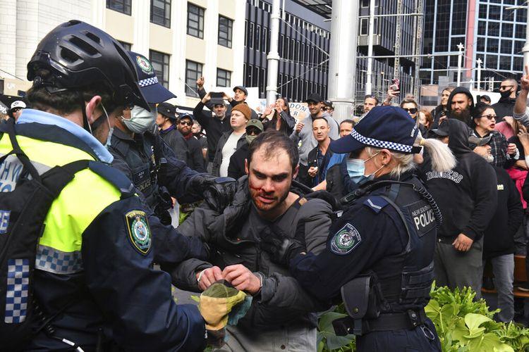 Seorang pengunjuk rasa, tengah, ditangkap oleh polisi dalam demonstrasi di Balai Kota Sydney selama demonstrasi anti-lockdown 'World Wide Rally For Freedom' di Sydney, Sabtu, 24 Juli 2021.