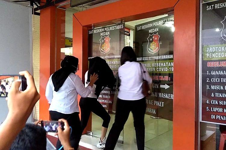Tangkapan layar video saat artis FTV berinisial H (23) memasuki gedung Satreskrim Polrestabes Medan usai pemeriksaan kesehatan dan Covid-19 di RS Bhayangkara Medan pada Senin (13/7/2020) sore. Kapolrestabes Medan Kombes Pol Riko Sunarko menyebut bahwa dalam kasus ini H sudah menerima uang puluhan juta.